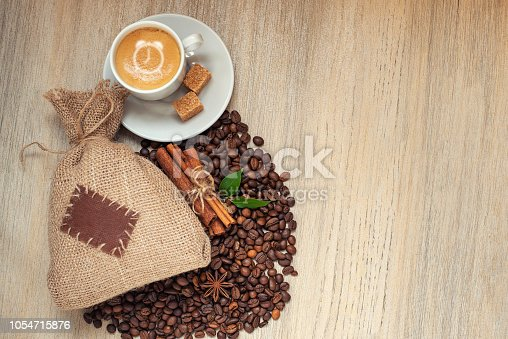 istock Cup with espresso with coffee beans, burlap sack and cinnamon on light wooden background 1054715876