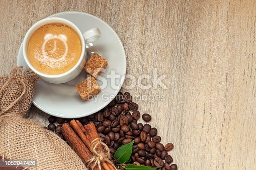 istock Cup with espresso with coffee beans, burlap sack, cinnamon alarm clock sign on light wooden background 1052047426
