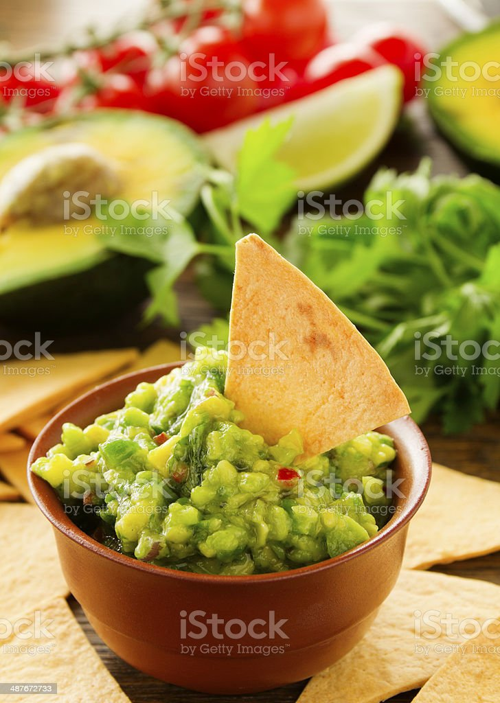 cup with guacamole and corn chips - traditional Mexican appetizer stock photo