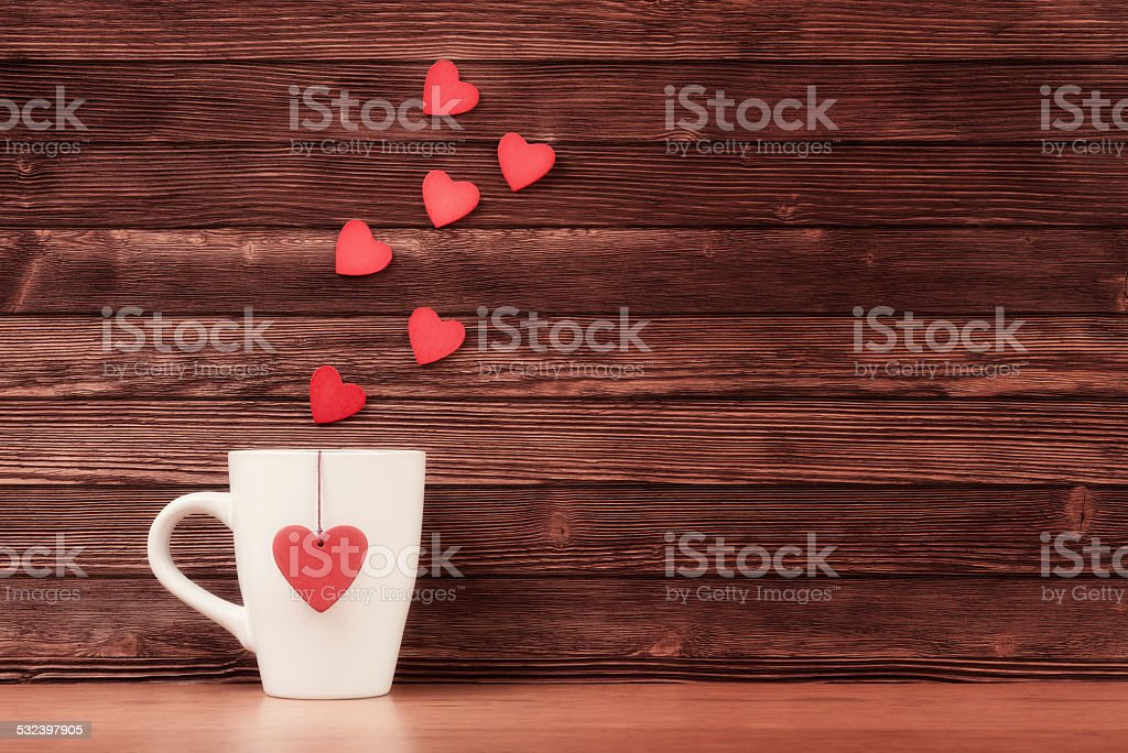 Cup with heart shapes over wooden background
