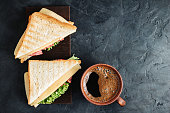 Cup with hot coffee and sandwich with grilled toast, salami sausage, salad lettuce and cheese on dark background, top view.