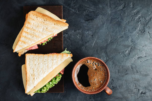 cup with hot coffee and sandwich with grilled toast, salami sausage, salad lettuce and cheese on dark background, top view - panino ripieno foto e immagini stock