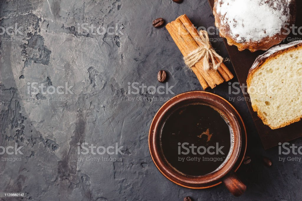 Cup with hot coffee, muffins and cinnamon sticks on the dark,...