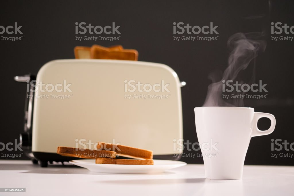 Cup With Hot Coffee Or Tea And A Toaster With A Delicious Slice Of Toasted Toast On The Kitchen Table On Black Background Breakfast In The Morning Stock Photo Download Image