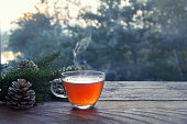 Cup with hot steaming tea on a rustic wooden garden table with Christmas decoration on a winter day, health concept against cold and flu, copy space, selected focus