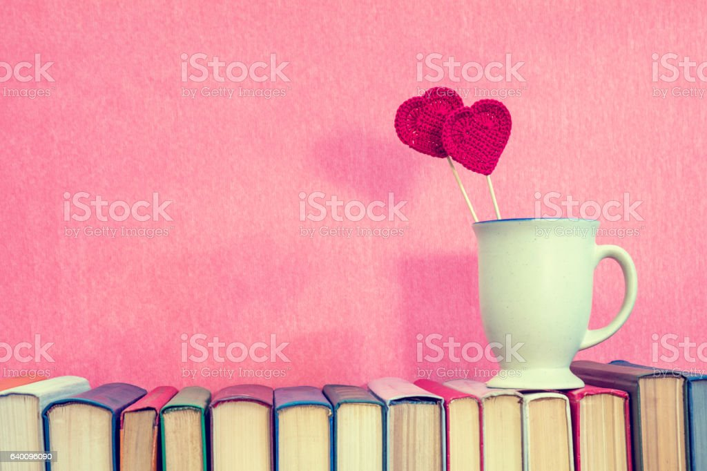 Cup with red crochet hearts on books stock photo