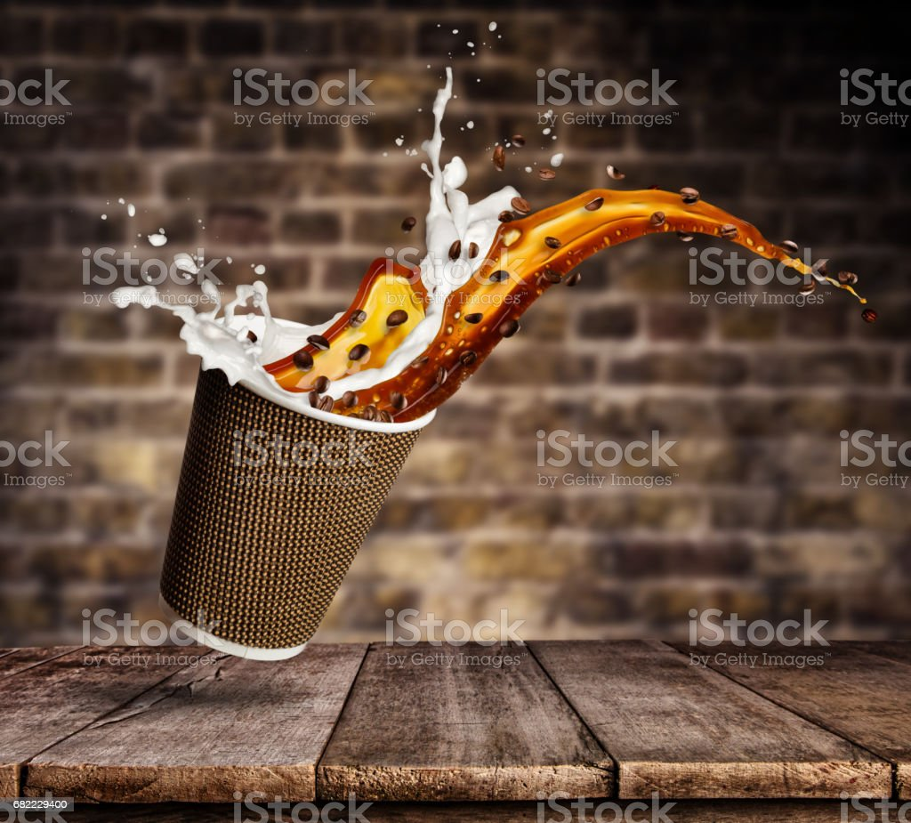 Cup with splashing coffee and milk liquid on wooden table. Take away hot drink stock photo