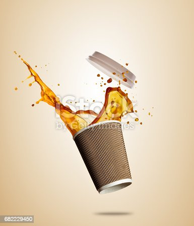istock Cup with splashing coffee or tea liquid separated on brown background. Take away hot drink 682229450
