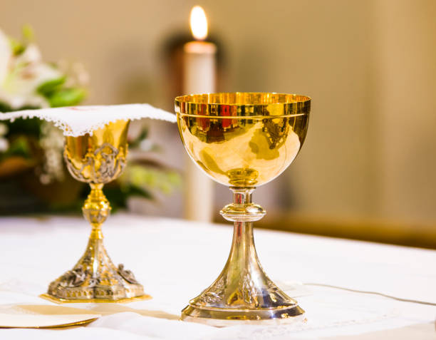 cup with wine and ciborium with host on the altar of the holy mass stock photo