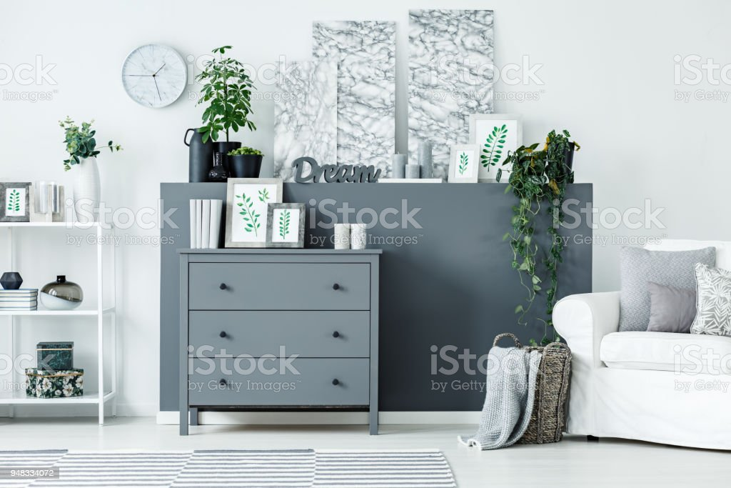 Grey wooden cupboard with books, framed posters and decor standing in...