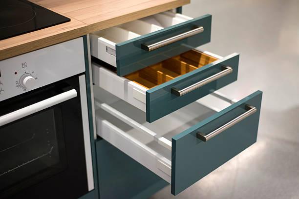 cupboard with opened empty drawers - griffe für küchenschränke stock-fotos und bilder