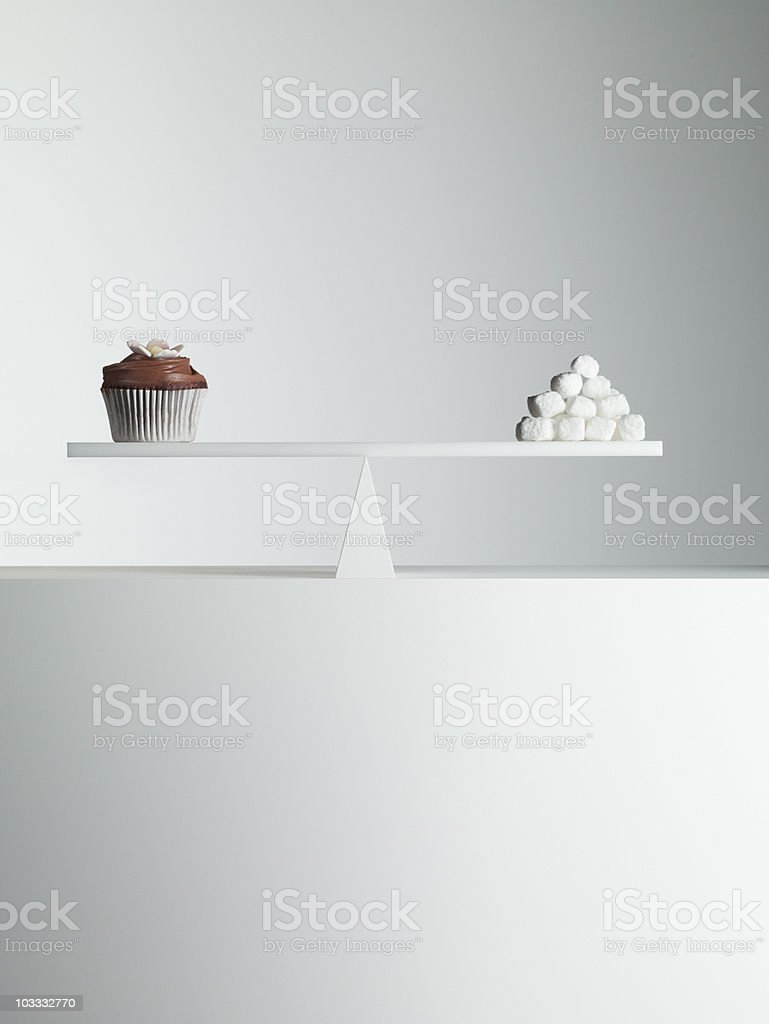 Cupcake and stack of sugar cubes balanced on seesaw stock photo