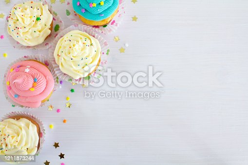 Vanilla buttercream cupcakes with sprinkles, on a white wooden table.