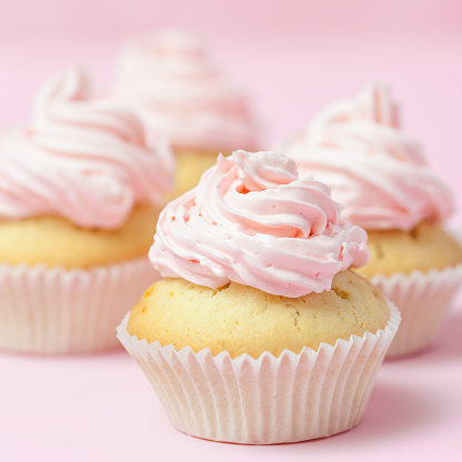 istock Cupcake decorated with pink buttercream on pastel pink background. Sweet beautiful cake. Square banner, greeting card for birthday, wedding, women's day. Close up photography. Selective focus 928162784