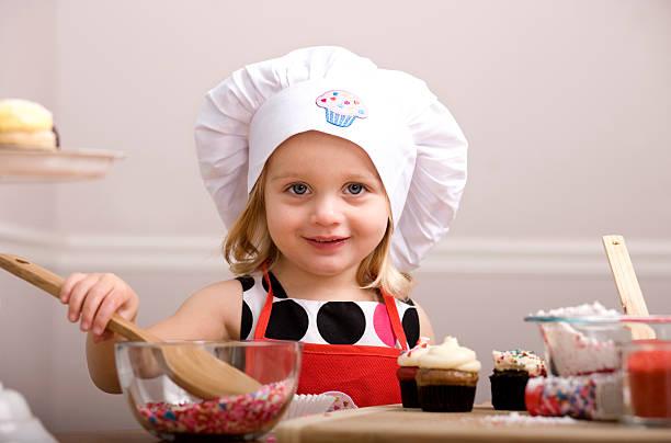 cupcakes dekorieren von kleinen mädchen in koch-mütze und schürze - 3 zutaten kuchen stock-fotos und bilder