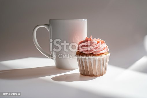 istock A cupcake or muffin stands next to a cup of coffee. 1323630894