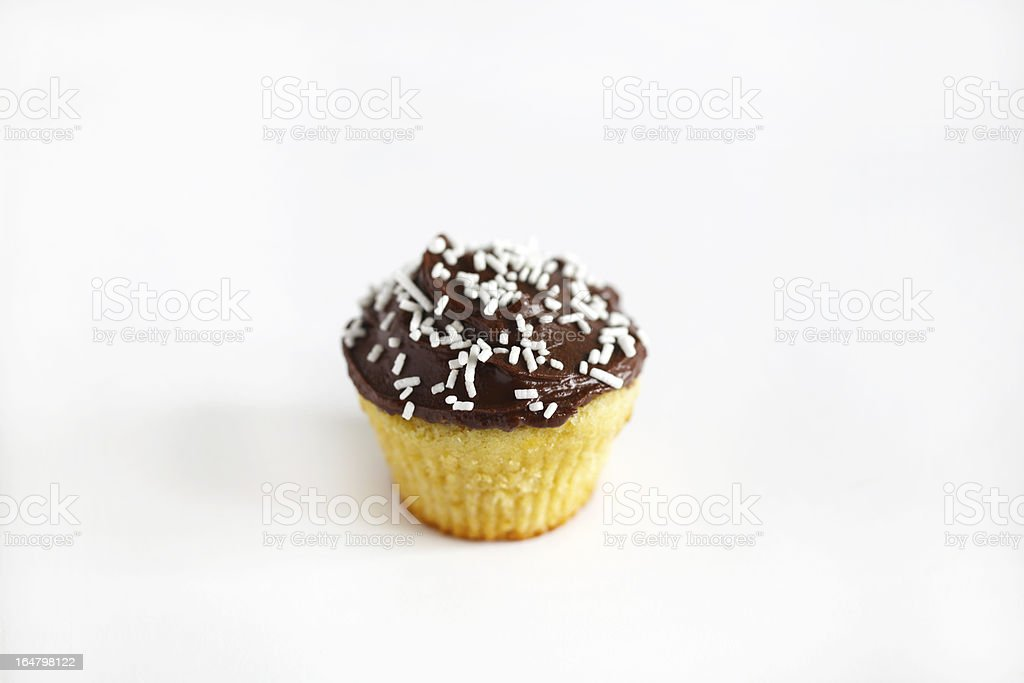 Cupcake or muffin with chocolate icing and sprinkles, isolated royalty-free stock photo