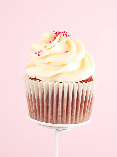 Cupcake Delicious cupcake topped with buttercream. Pink background. buttercream stock pictures, royalty-free photos & images