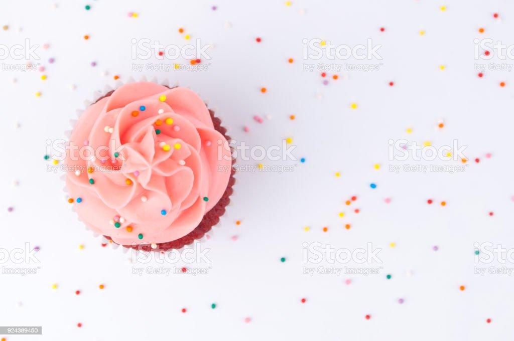 Velvet Cupcake rouge avec Chantilly bleu et rose ornée de paillettes colorées. photo libre de droits