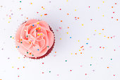 Cupcake red velvet with blue and pink whipped cream decorated with colorful sprinkles on white background. Top view.