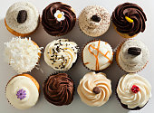 Subject: Horizontal high angle, directly overhead view of a dozen frosted cupcakes. The cupcakes are against a white background and are decorated with swirls, sprinkles, drizzles and candies—a tempting decadent treat for those who indulge in sweets and love cakes with lots of toppings.