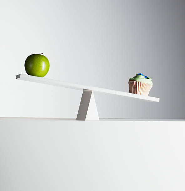 Cupcake tipping seesaw with green apple on opposite end stock photo