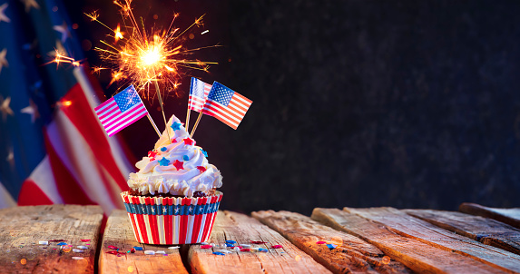 Cupcake Usa Celebration With American Flags And Sparkler On Wooden Table