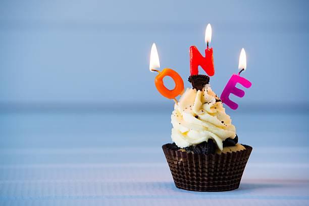 cupcake with a candles for 1 - first birthday - nummer 1 kuchen stock-fotos und bilder
