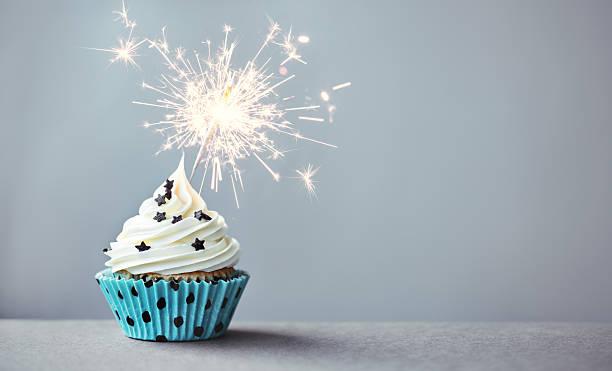 cupcake mit wunderkerze - kindergeburtstagskuchen stock-fotos und bilder