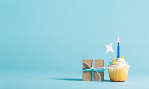 cupcake mit kerze und geschenkbox - tortenfiguren stock-fotos und bilder