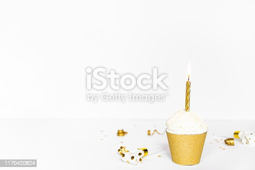 istock Cupcake with lighted candle and party accessories in golden color. 1170420824