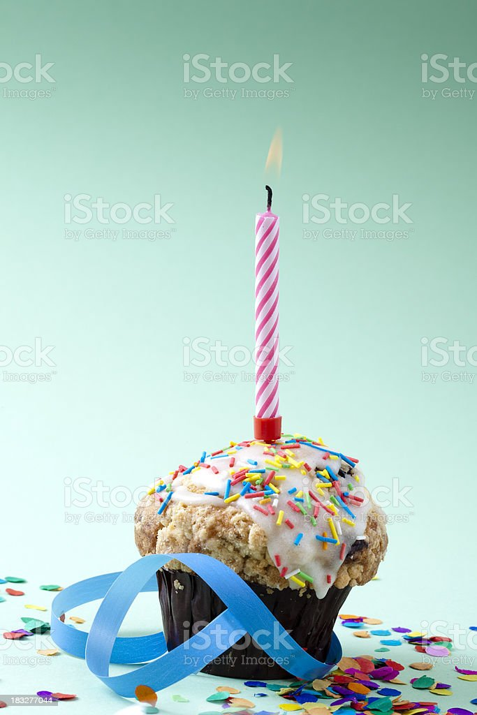 Cupcake with lit candle and confetti royalty-free stock photo