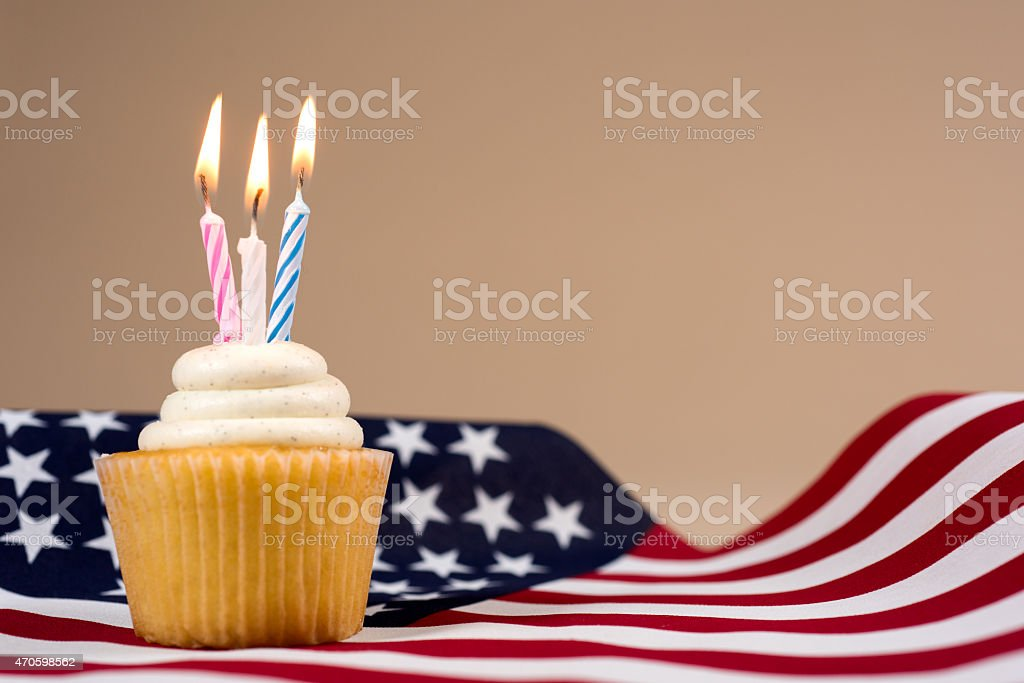 Cupcake with lit Candles on American Flag stock photo