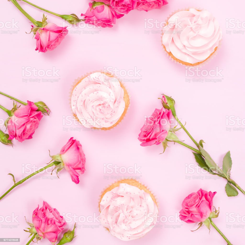 Cupcake with pink cream decoration and roses on pink pastel background. stock photo