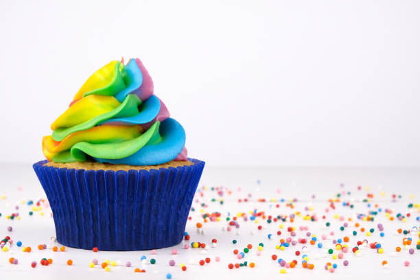 cupcake with rainbow colorful cream in blue cup on white wooden table decorated with colorful sprinkles. - posypka zdjęcia i obrazy z banku zdjęć