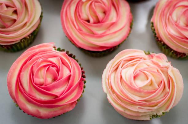 cupcake mit rosa buttercreme zuckerguss - rosentorte stock-fotos und bilder