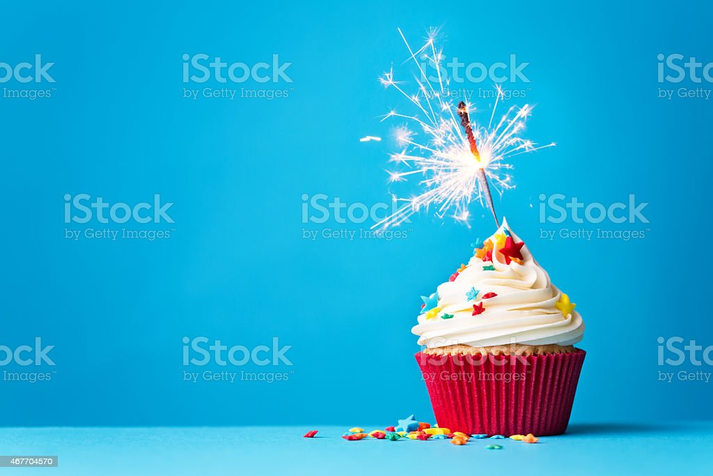 Cupcake with sparkler on blue stock photo