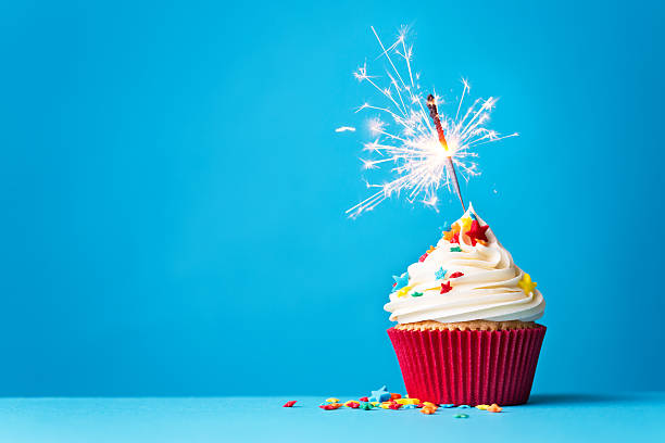 Cupcake with sparkler on blue Cupcake with sparkler against a blue background cupcake stock pictures, royalty-free photos & images