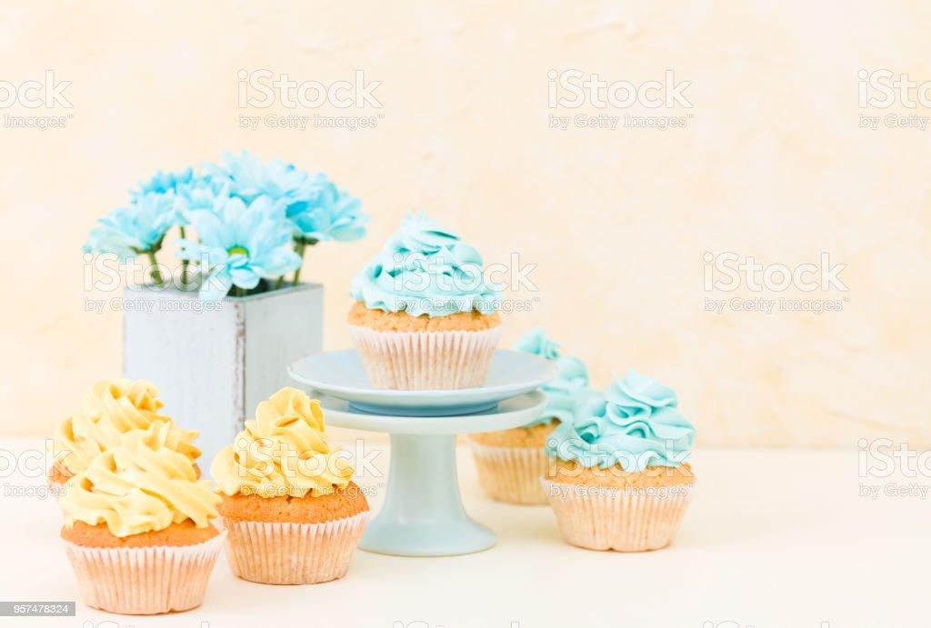 Cupcake com buttercream azul e amarelo doce decoração e azul crisântemo em vaso chique gasto retrô. - Foto de stock de Alimentação Não-saudável royalty-free