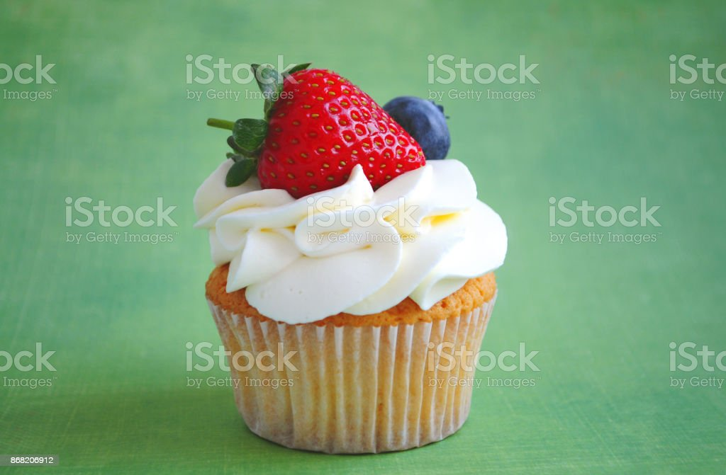 Cupcake with whipped cream, fresh strawberry, blueberry on green background. stock photo