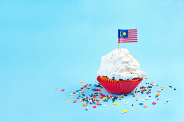 Cupcake with White Topping Happy Malaysia Day, August 31th and Malaysia flag on blue background stock photo