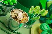 This is a photograph of cupcakes and candy on  a green background for St. Patrick's day.