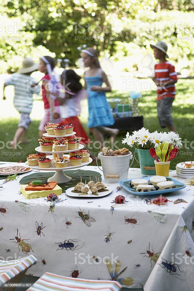 Cupcakes and desserts on table, children (6-11) playing in background foto de stock libre de derechos