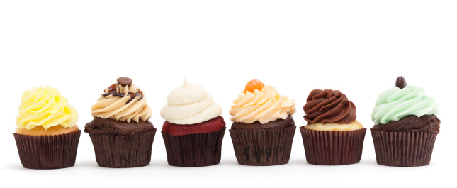 Photograph of 6 pretty, gourmet cupcakes in a row on a white background; copy space