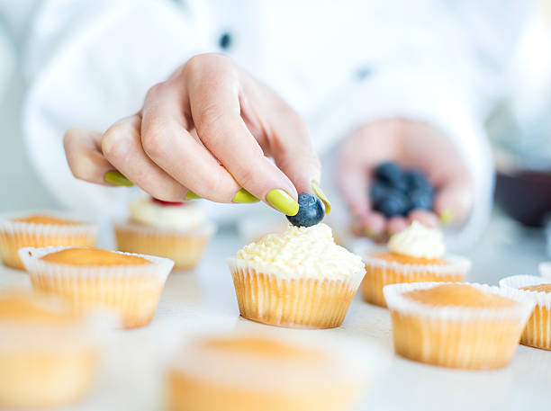 close up of woman in bakery decorating cake with icing stock photo cupcakes stock photo - Woman Decorating Cupcakes