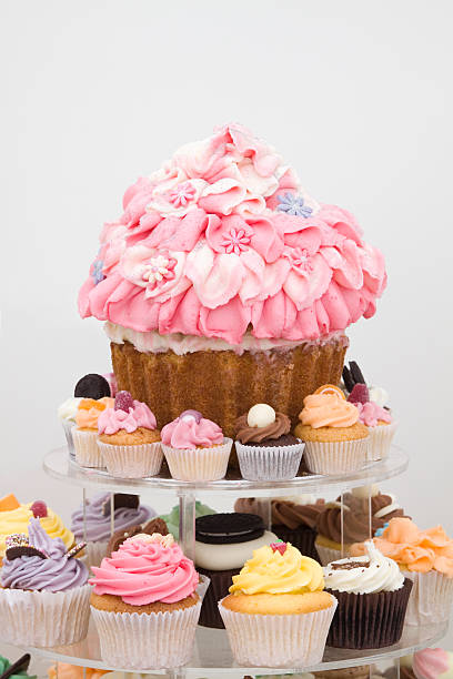 cupcakes small medium and large - big cake stock photos and pictures
