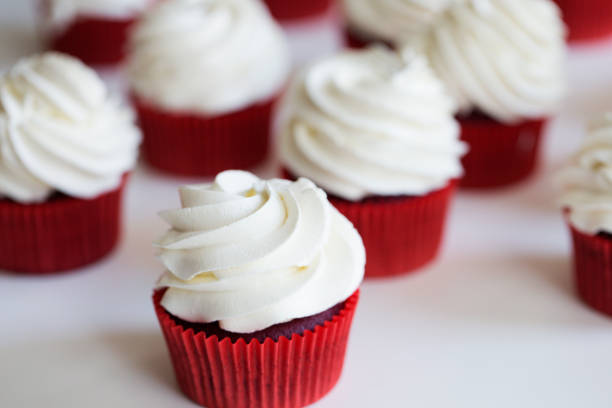 cupcakes topped with swirl of sweet vanilla frosting. Red velvet cupcakes cupcakes topped with swirl of sweet vanilla frosting. Red velvet cupcakes buttercream stock pictures, royalty-free photos & images
