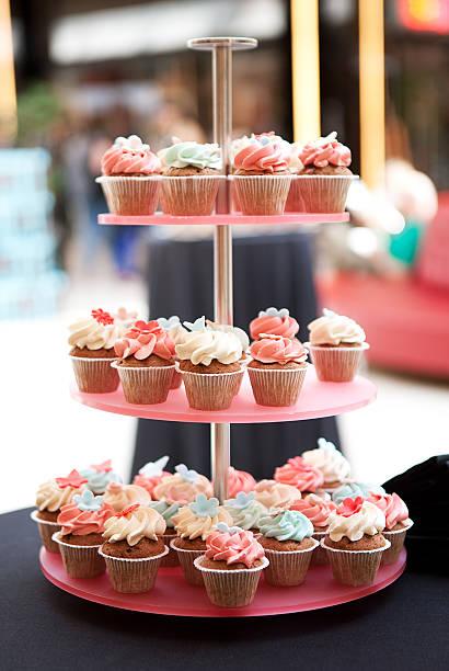 cupcakes tower mit zuckerguss auf verwischen hintergrund garnieren - cupcake türme stock-fotos und bilder