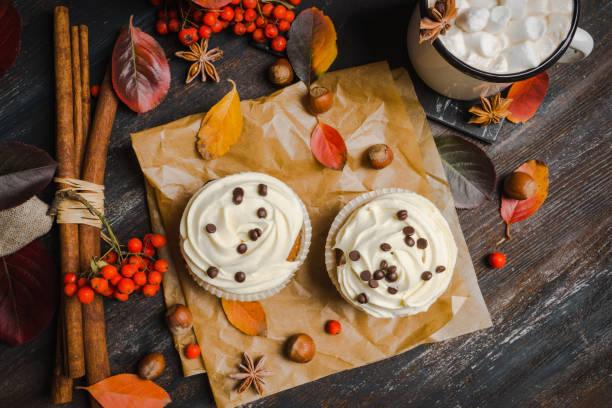cupcakes mit herbstlichen dekorationen auf dem rustikalen hölzernen hintergrund - heiße schokoladen cupcakes stock-fotos und bilder