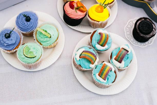 cupcakes mit bunten sahne und früchten - regenbogen käsekuchen stock-fotos und bilder